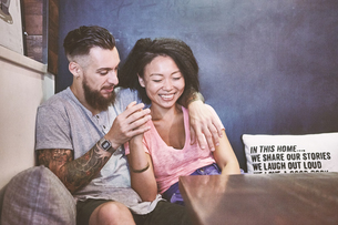 Multi ethnic hipster couple in cafe laughing, Shanghai French Concession, Shanghai, Chinaの写真素材 [FYI03601102]