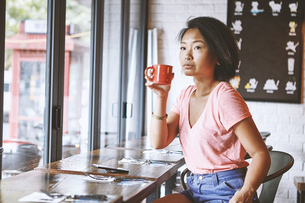 Woman in cafe watching from window seat, Shanghai French Concession, Shanghai, Chinaの写真素材 [FYI03601107]