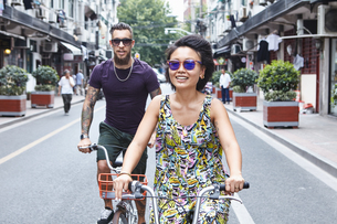 Multi ethnic hipster couple cycling along city street, Shanghai French Concession, Shanghai, Chinaの写真素材 [FYI03601112]
