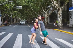 Woman pushing boyfriend on pedestrian crossing, Shanghai French Concession, Shanghai, Chinaの写真素材 [FYI03601123]