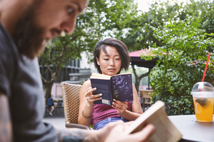 Multi ethnic hipster couple reading books at sidewalk cafe, Shanghai French Concession, Shanghai, Chの写真素材 [FYI03601130]