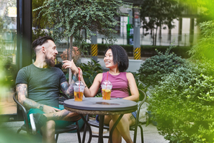 Multi ethnic hipster couple talking at sidewalk cafe, Shanghai French Concession, Shanghai, Chinaの写真素材 [FYI03601131]