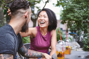 Multi ethnic hipster couple laughing at sidewalk cafe, Shanghai French Concession, Shanghai, Chinaの写真素材 [FYI03601134]