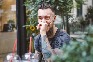 Young male hipster laughing at sidewalk cafe, Shanghai French Concession, Shanghai, Chinaの写真素材 [FYI03601137]
