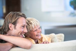 Father and son relaxing on sofa, looking away smilingの写真素材 [FYI03601219]