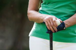 Cropped view of woman wearing golf glove holding golf ball and clubの写真素材 [FYI03601262]
