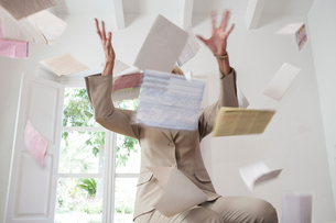 Businesswoman throwing paperwork in airの写真素材 [FYI03601267]