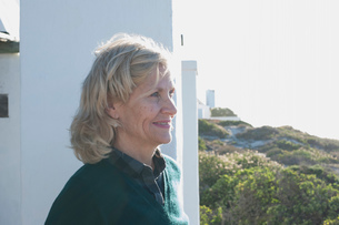 Happy blond haired senior woman looking out from sunlit coastal home, Cape Town, Western Cape, Southの写真素材 [FYI03601345]