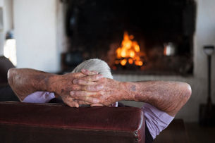 Rear view of senior man at home with hands behind his head in front of log fireの写真素材 [FYI03601352]