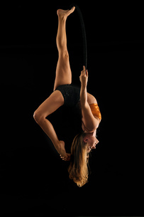 Young female aerial acrobat hanging upside down from hoop against black backgroundの写真素材 [FYI03601415]