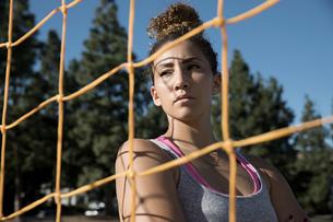 Portrait of woman behind football goal netting looking awayの写真素材 [FYI03601516]