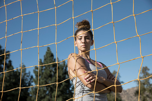 Portrait of woman behind football goal netting looking at cameraの写真素材 [FYI03601518]