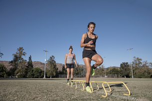 Woman jumping over agility hurdlesの写真素材 [FYI03601537]