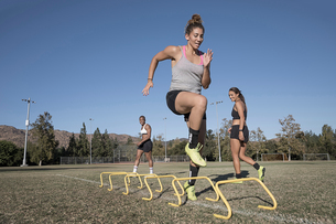 Woman jumping over agility hurdlesの写真素材 [FYI03601542]