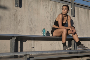 Portrait of woman in sport clothing sitting on bench looking awayの写真素材 [FYI03601549]