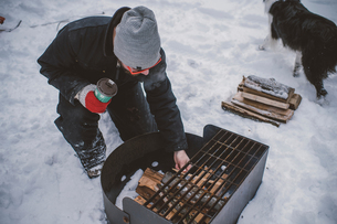 Young man preparing to light barbecue fire in snowの写真素材 [FYI03601559]