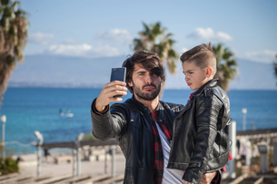 Father and son outdoors, father taking selfie using smartphoneの写真素材 [FYI03601768]
