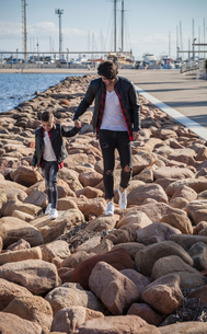 Father and son walking on rocks beside seaの写真素材 [FYI03601770]