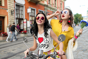 Portrait of two happy female friends wearing sunglasses riding scooter on cobbled street, Odessa, Ukの写真素材 [FYI03601895]