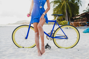Neck down view of young woman with bicycle on sandy beach, Krabi, Thailandの写真素材 [FYI03601903]
