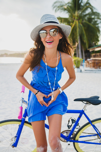 Portrait of young woman with bicycle making heart shape with hands on sandy beach, Krabi, Thailandの写真素材 [FYI03601904]