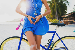 Neck down view of young woman with bicycle making heart shape with hands on sandy beach, Krabi, Thaiの写真素材 [FYI03601906]
