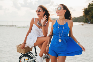 Two young women in sundresses with bicycle on sandy beach, Krabi, Thailandの写真素材 [FYI03601907]
