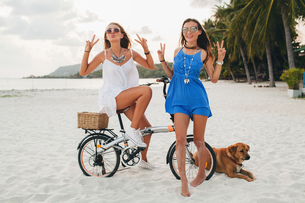 Portrait of two young women with bicycle making peace sign on sandy beach, Krabi, Thailandの写真素材 [FYI03601908]