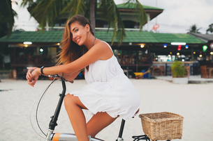 Portrait of young woman leaning on bicycle handlebars on sandy beach, Krabi, Thailandの写真素材 [FYI03601912]