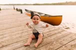 Portrait of baby girl sitting on lake pierの写真素材 [FYI03601957]