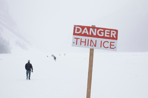 Danger sign and people on frozen Lake Louise, Canadaの写真素材 [FYI03602032]