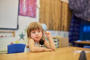 Primary schoolgirl fiddling with hair at classroom deskの写真素材 [FYI03602089]