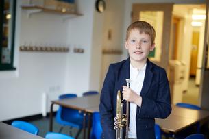 Primary schoolboy holding trumpet in classroom, portraitの写真素材 [FYI03602096]