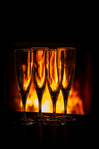 Four champagne glasses on table in front of burning fireの写真素材 [FYI03602233]