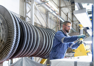Engineer at workstation with high pressure steam turbine in turbine maintenance factoryの写真素材 [FYI03602254]