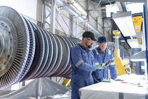 Engineers inspecting turbine blade in turbine maintenance factoryの写真素材 [FYI03602257]