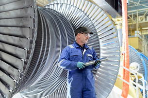 Engineer with turbine blade in turbine maintenance factoryの写真素材 [FYI03602261]
