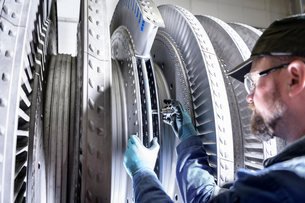 Close up of engineer working on high pressure steam turbine in turbine maintenance factoryの写真素材 [FYI03602262]