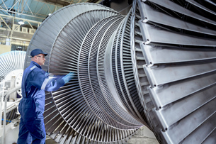 Engineer turning low pressure steam turbine during inspection in turbine maintenance factoryの写真素材 [FYI03602265]