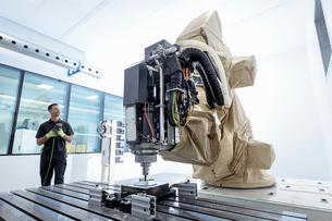 Apprentice robotics engineer with robot in robotics research facilityの写真素材 [FYI03602278]