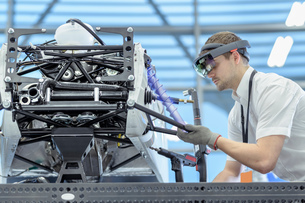 Engineer using augmented reality headset to 'see' parts position on car in assembly composite imageの写真素材 [FYI03602300]