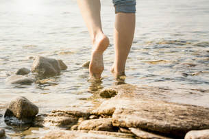 Cropped view of woman barefoot in waterの写真素材 [FYI03602399]