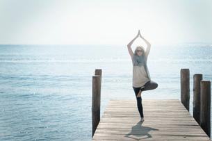 Woman on pier balancing on one leg in yoga poseの写真素材 [FYI03602404]