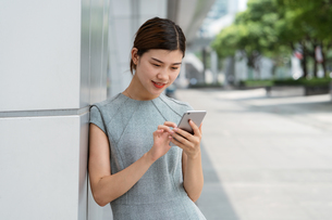 Young businesswoman using smartphone touchscreen in city, Shanghai, Chinaの写真素材 [FYI03602461]