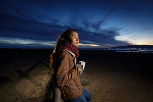 Young woman wrapped in scarf looking out from beach at dusk, Tarragona, Catalonia, Spainの写真素材 [FYI03602482]