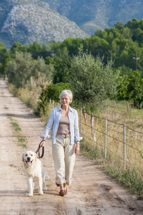 Portrait of senior woman walking pet dogの写真素材 [FYI03602867]