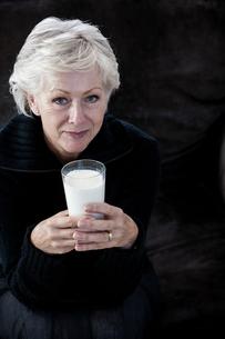 Portrait of senior woman, holding glass of milkの写真素材 [FYI03602874]