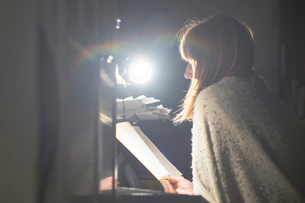 Woman reading at desk by table lampの写真素材 [FYI03602914]