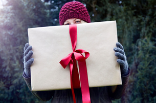Woman holding up Christmas present with red ribbonの写真素材 [FYI03603112]