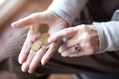 Senior woman counting coins in hand, close-upの写真素材 [FYI03603113]
